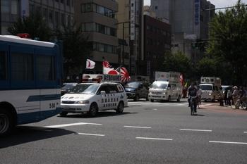 2009年8月15日 12時半頃、神保町交叉点、警察のバスに頭を抑えられ進む右翼の車。