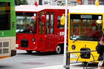 2020年3月28日 12時前。池袋。東口の前のIKEバス。通常の赤色と、1台だけいる黄色が並びました。