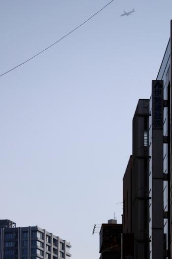 2021年8月28日 15時47分頃。池袋。もう1回、西武デパートの背後で旋回し、西武門番ビルの背後を通過するジョット機。